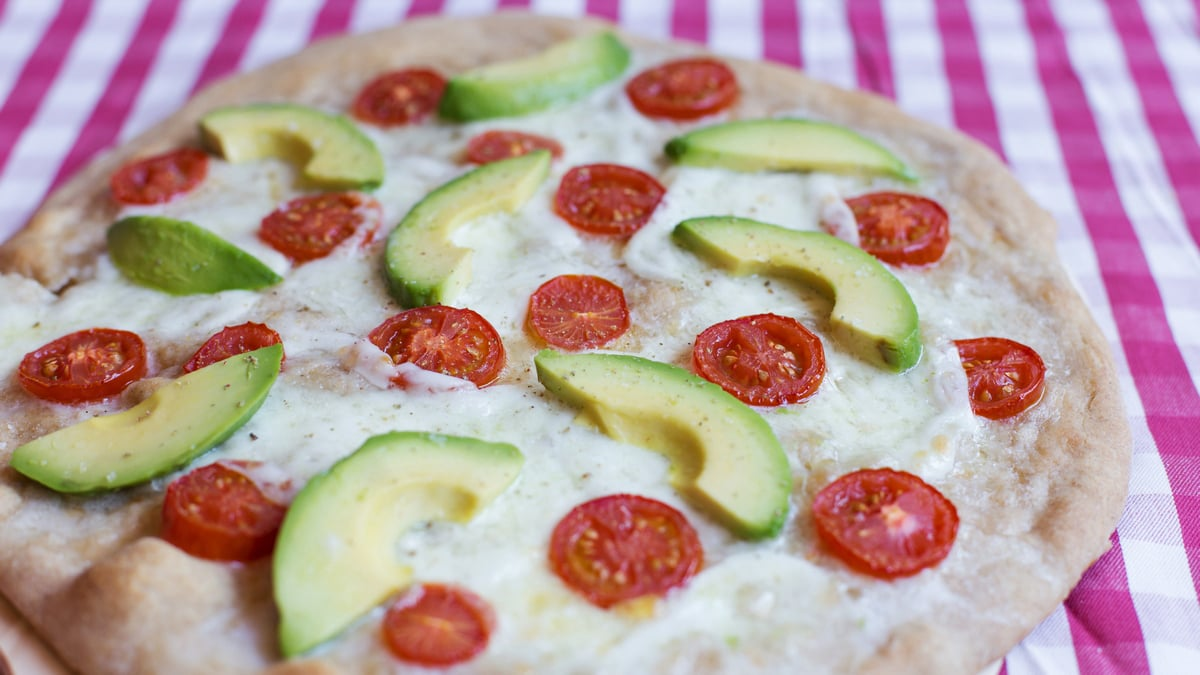 Home-made pizza with fresh tomatoes and avocado