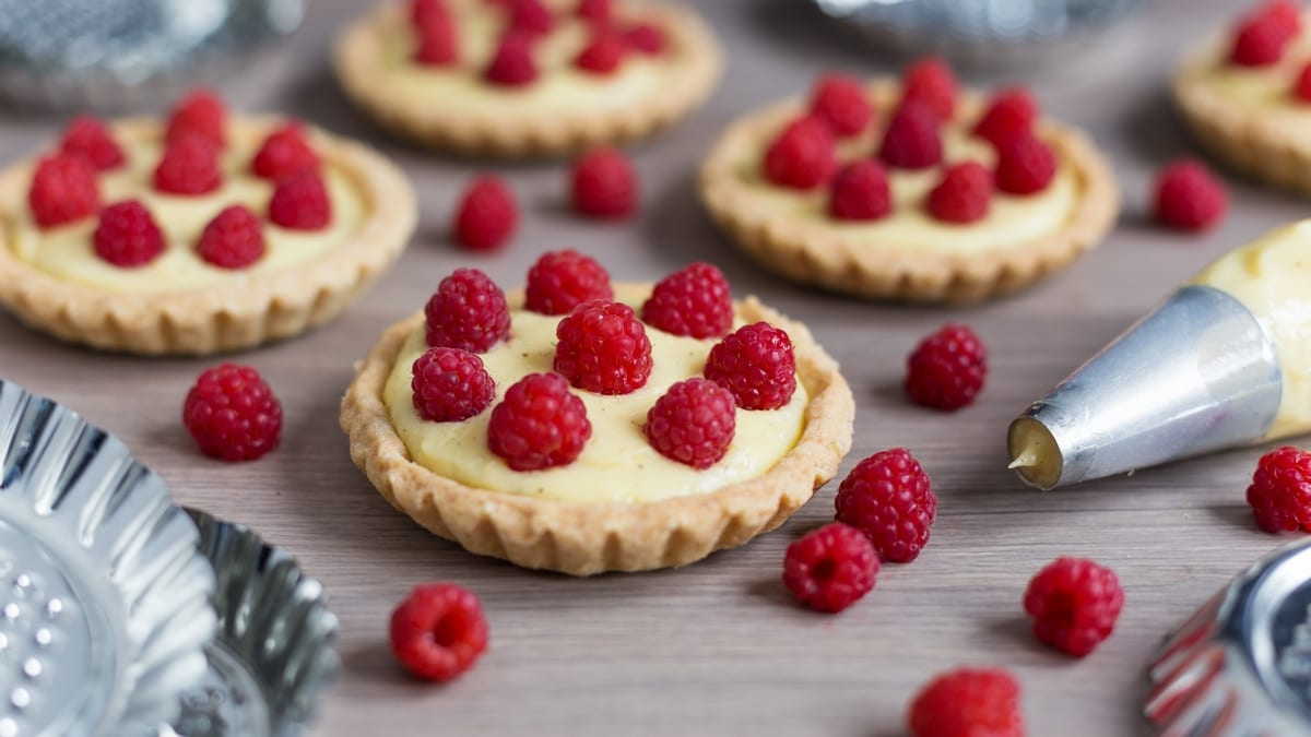 Home-made custard tarts decorated with freshly picked raspberries