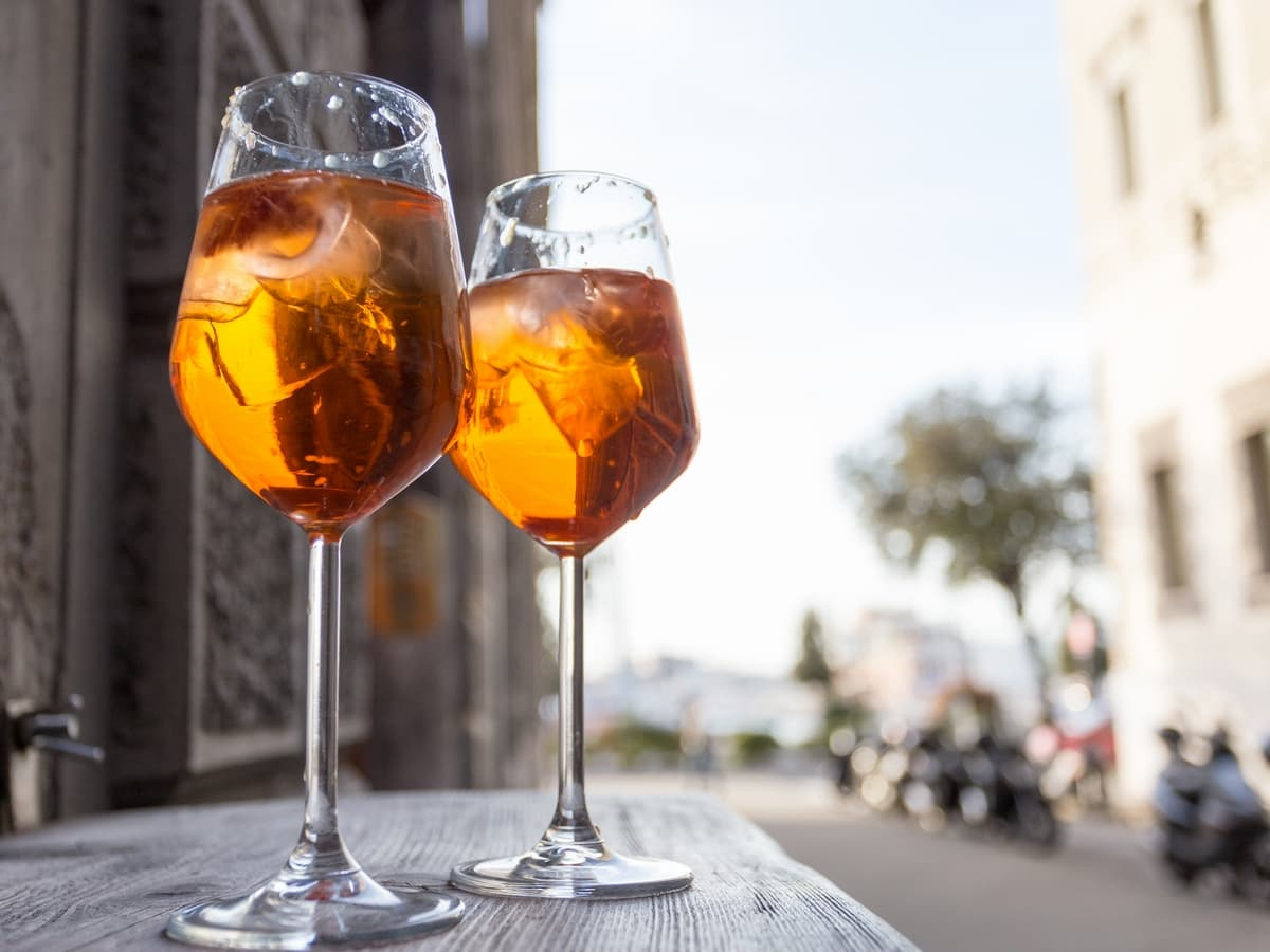 Two glasses filled with Aperol Spritz on the streets of Trieste.