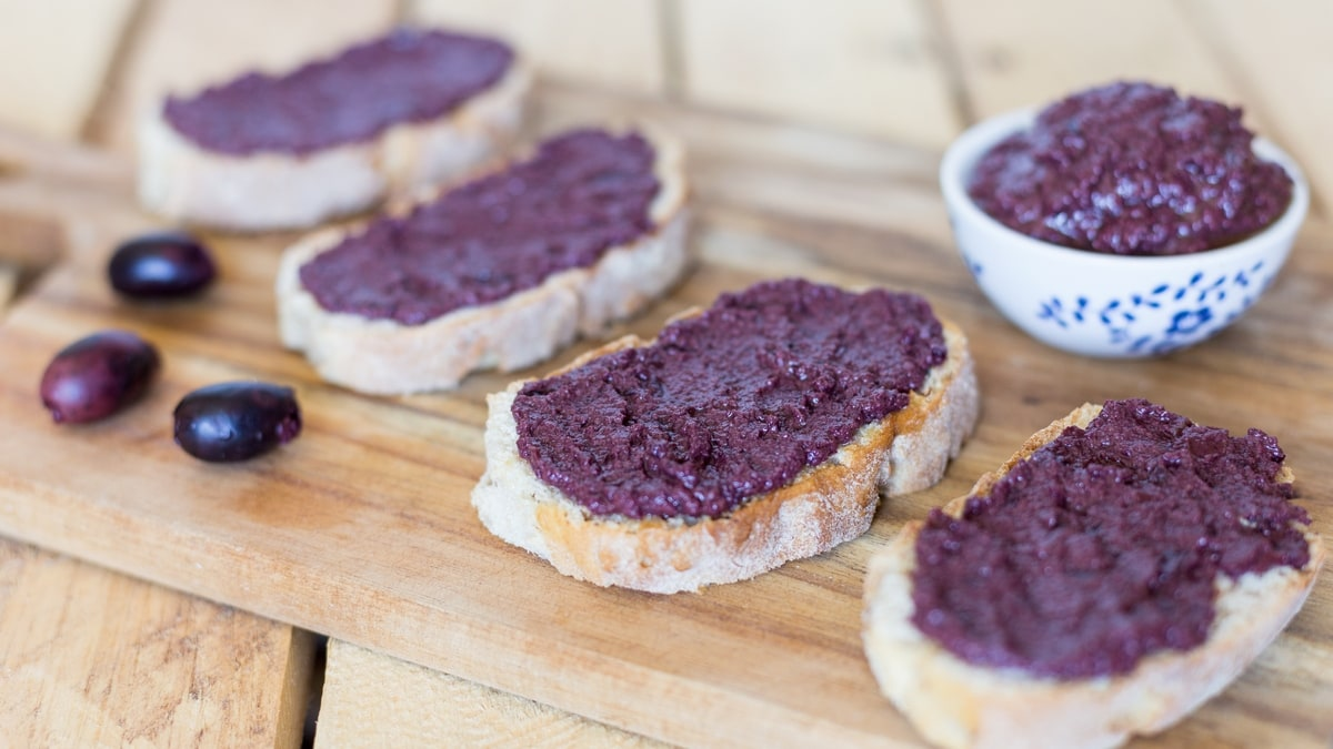 Black olive paté, or black olive paste, spread on bread is one of those lovely alternatives to the classic garlic and tomato bruchetta topping.