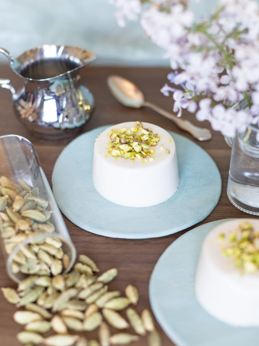 Vegan panna cotta with coconut milk and cardamom served on a blue plate with ground pistachio as decoration.