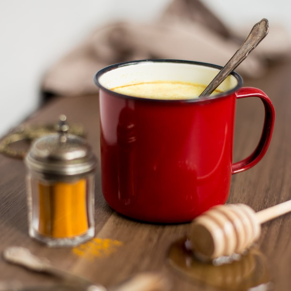 Hot milk with honey, rum and turmeric powder in a red enamel mug.