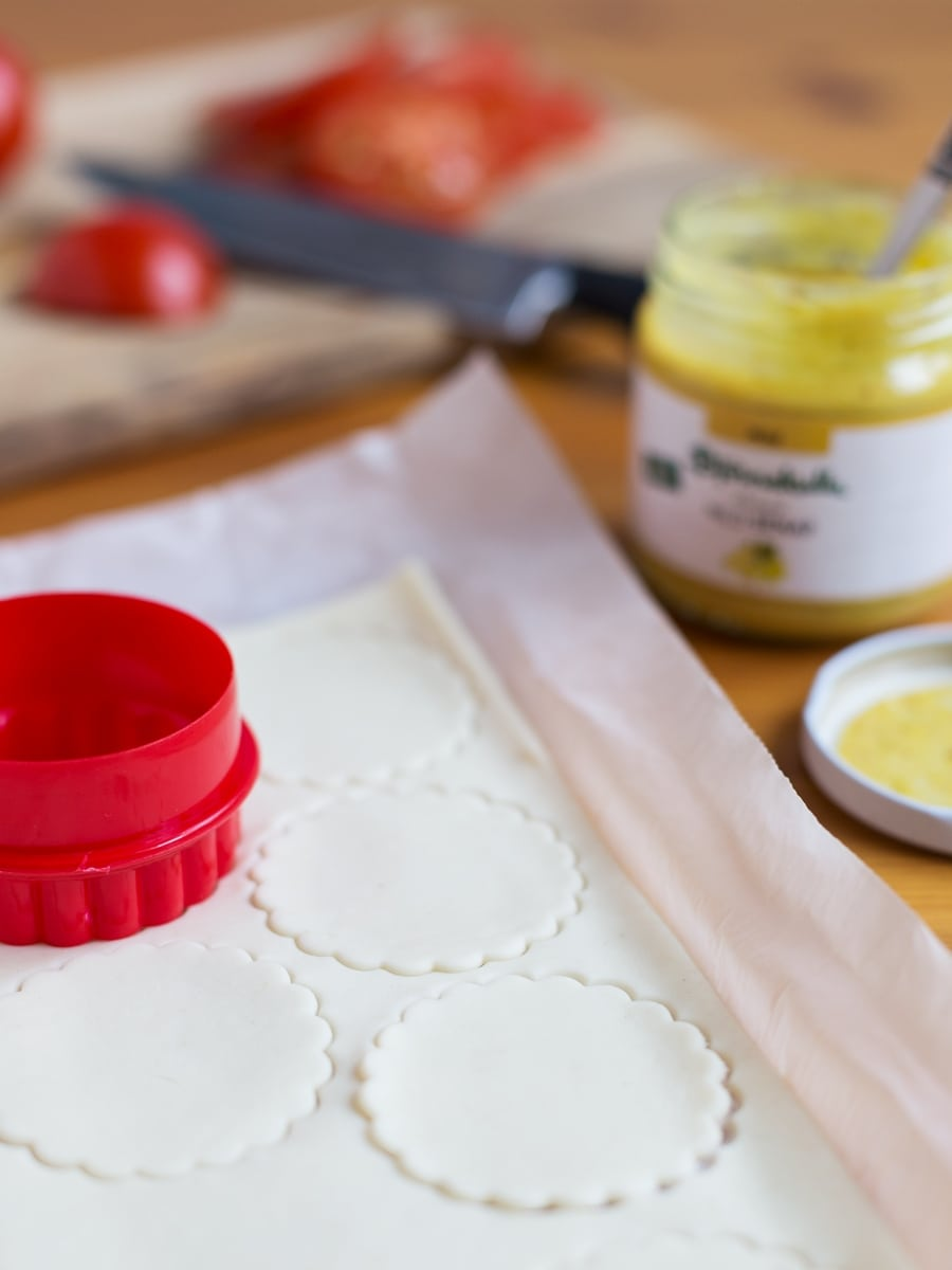 Puff pastry sheet being cut with a flower shaped cookie cutter.