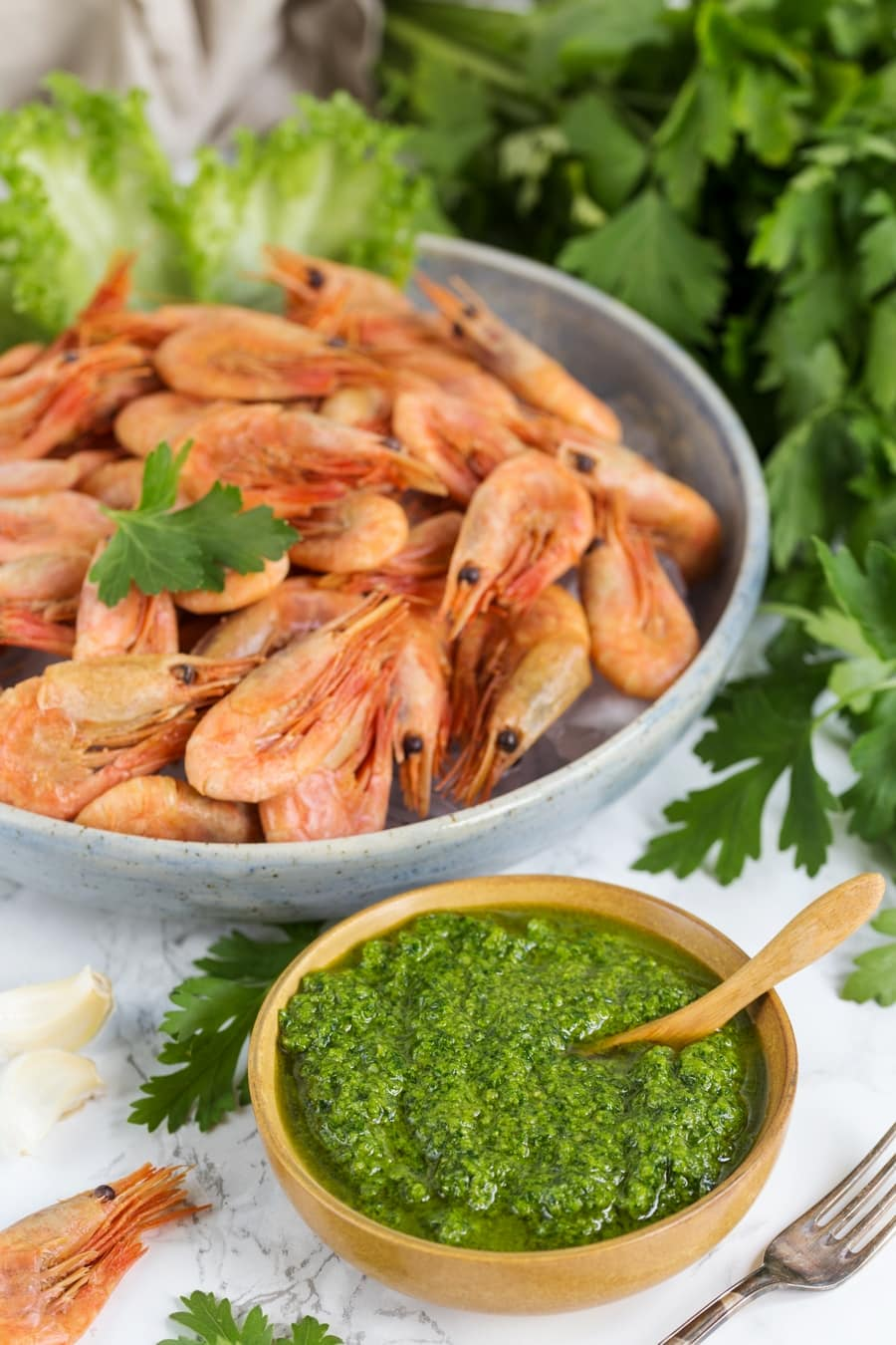 A small bowl of nordic pesto and a large bowl filled with smoked shrimp.