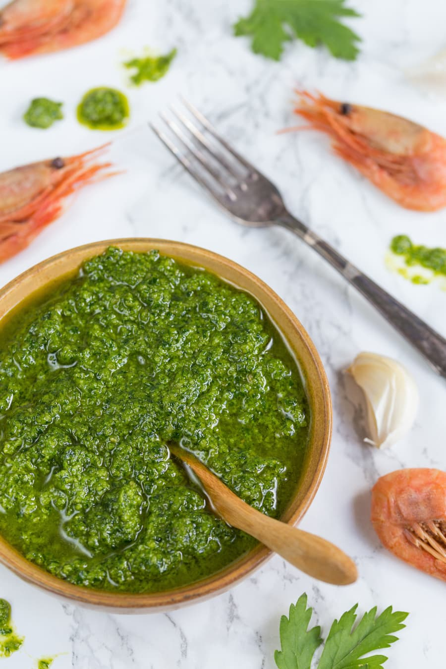 Bowl of pesto and shrimps on the table.