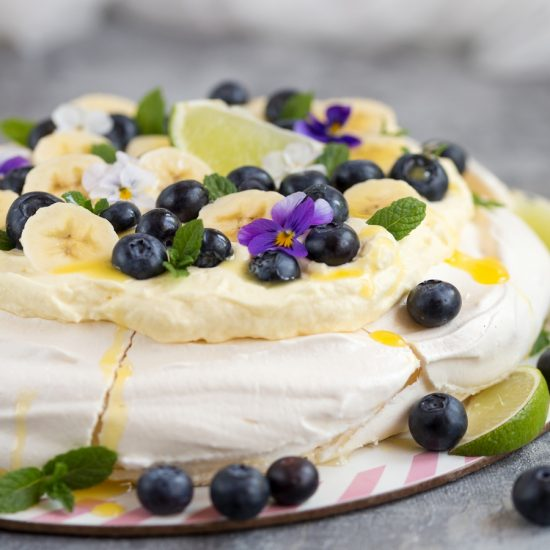 Australian cake pavlova with mango cream, blueberries, banana slices, pansies, mint leaves and lime curd drizzle.