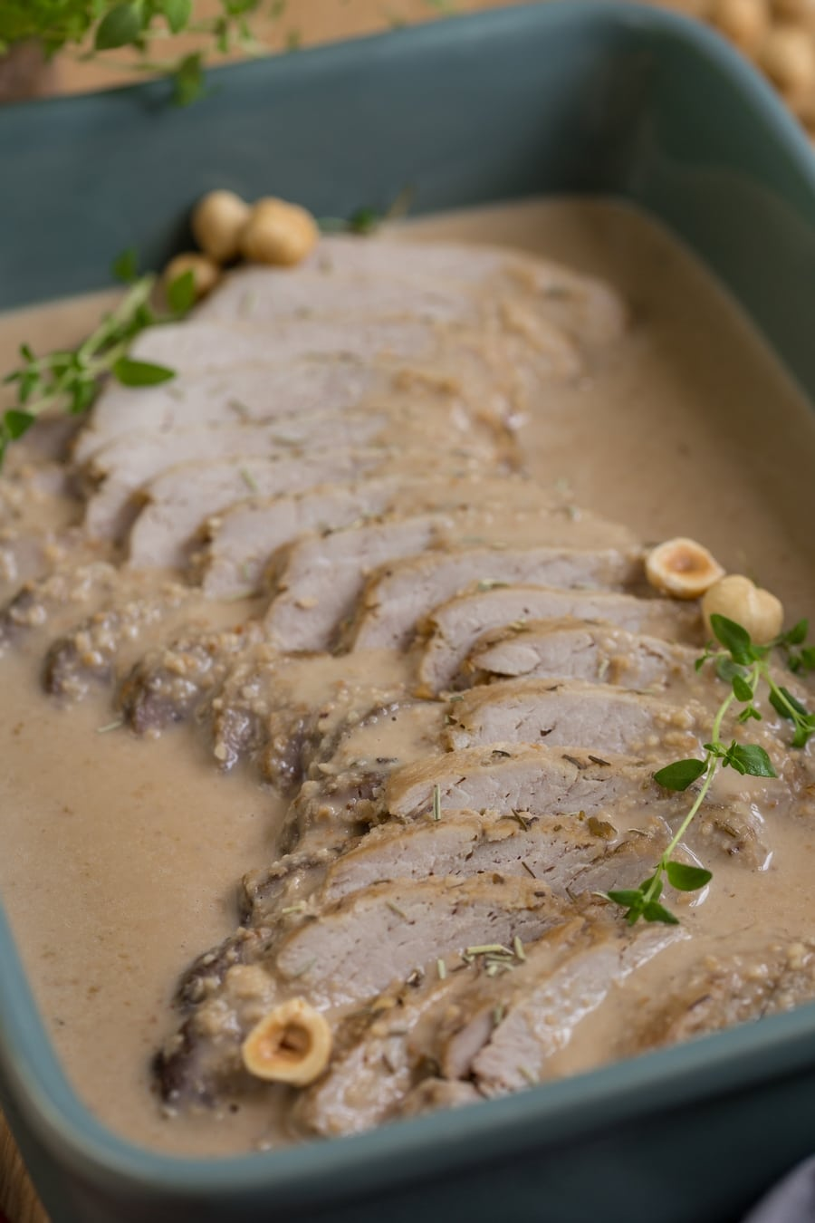 Baked pork loin in hazelnut sauce in green casserole dish.