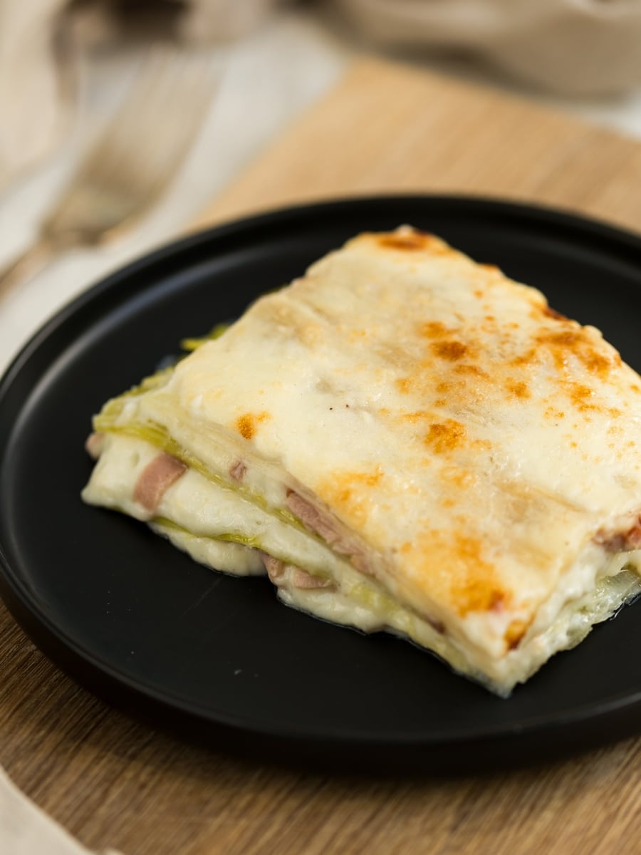 Slice of leek lasagna on black plate.