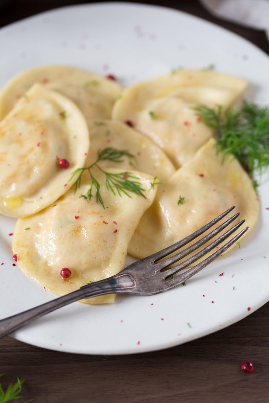 Smoked salmon ravioli with dill and pink peppercorns on a white plate.