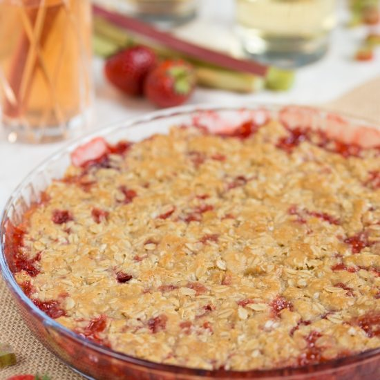 Baked strawberry rhubarb crisp, strawberry cocktails in the background.