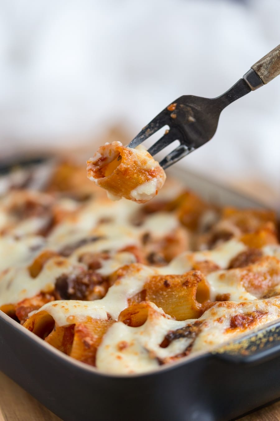 Fork lifting pasta piece from baked pasta casserole.