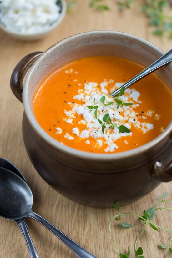 Orange pepper soup and white cheese crumbs in a brown clay pot, ladle in soup.