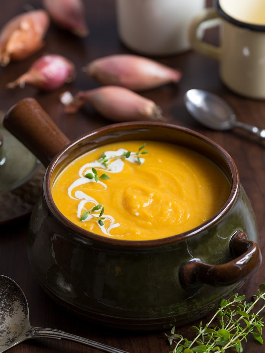 Pumpkin soup in a ceramic pot, shallots in the background.