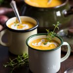 Roasted pumpkin and red lentil soup in enamel mugs, decorated with fresh thyme.