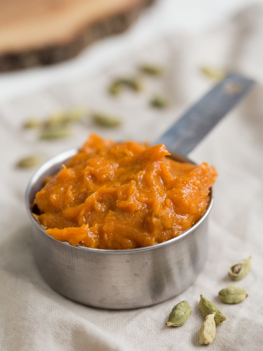 Roasted sweet potato mash in a half cup, cardamom pods around it.