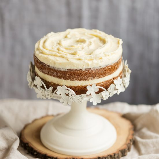 Frosted sweet potato cake on white cake stand.