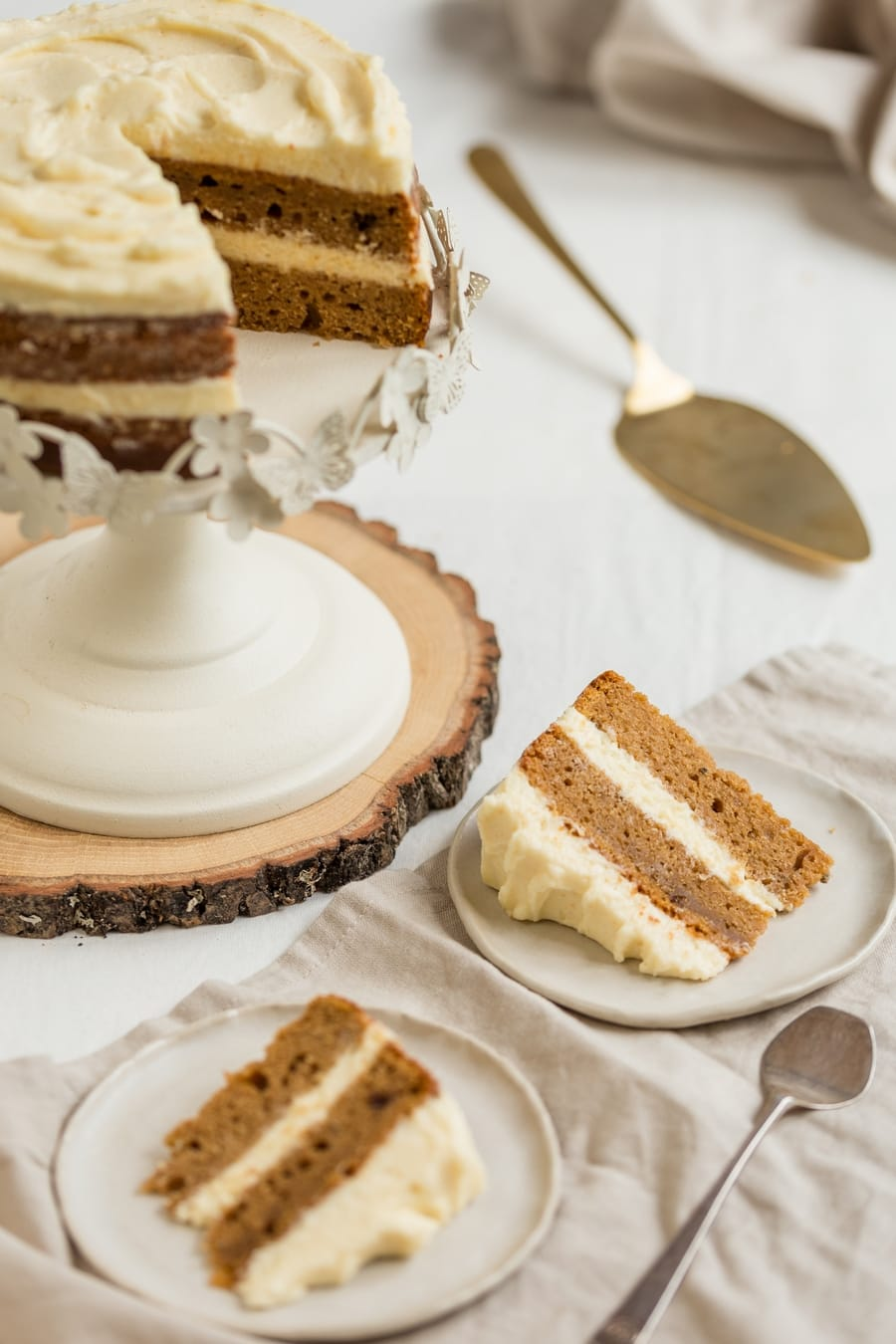 Sliced frosted cake, plated slices on the side.