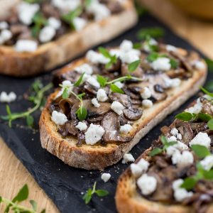 Closeup of garlicky mushroom crostini with crumbed goat cheese.