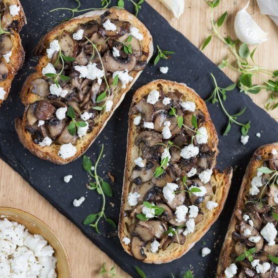 Garlicky mushroom crostini with crumbed goat cheese flat lay.