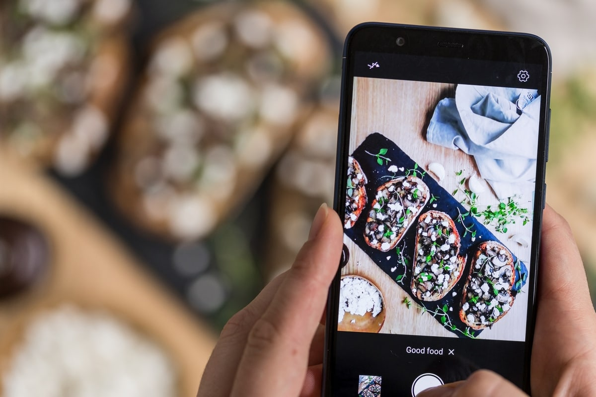 Mushroom crostini being photographed with a phone camera; phone in focus, food in the background.