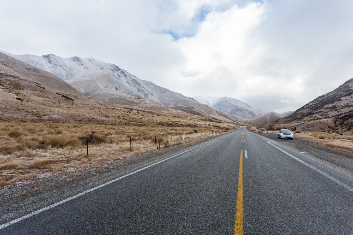 New Zealand South Island road with non self-contained van parked on the side.