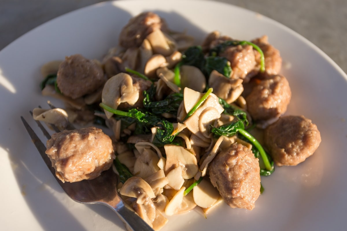 Cooked sauseage balls with mushrooms and spinach.
