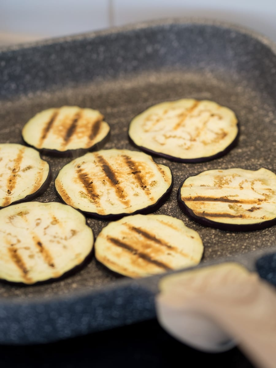 Eggplant slices in a grill skillet on the stove.