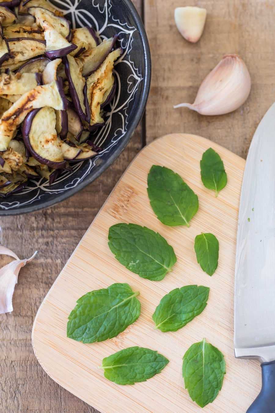 Fresh spearmint leaves on a cutting board, sliced grilled eggplant on the side.