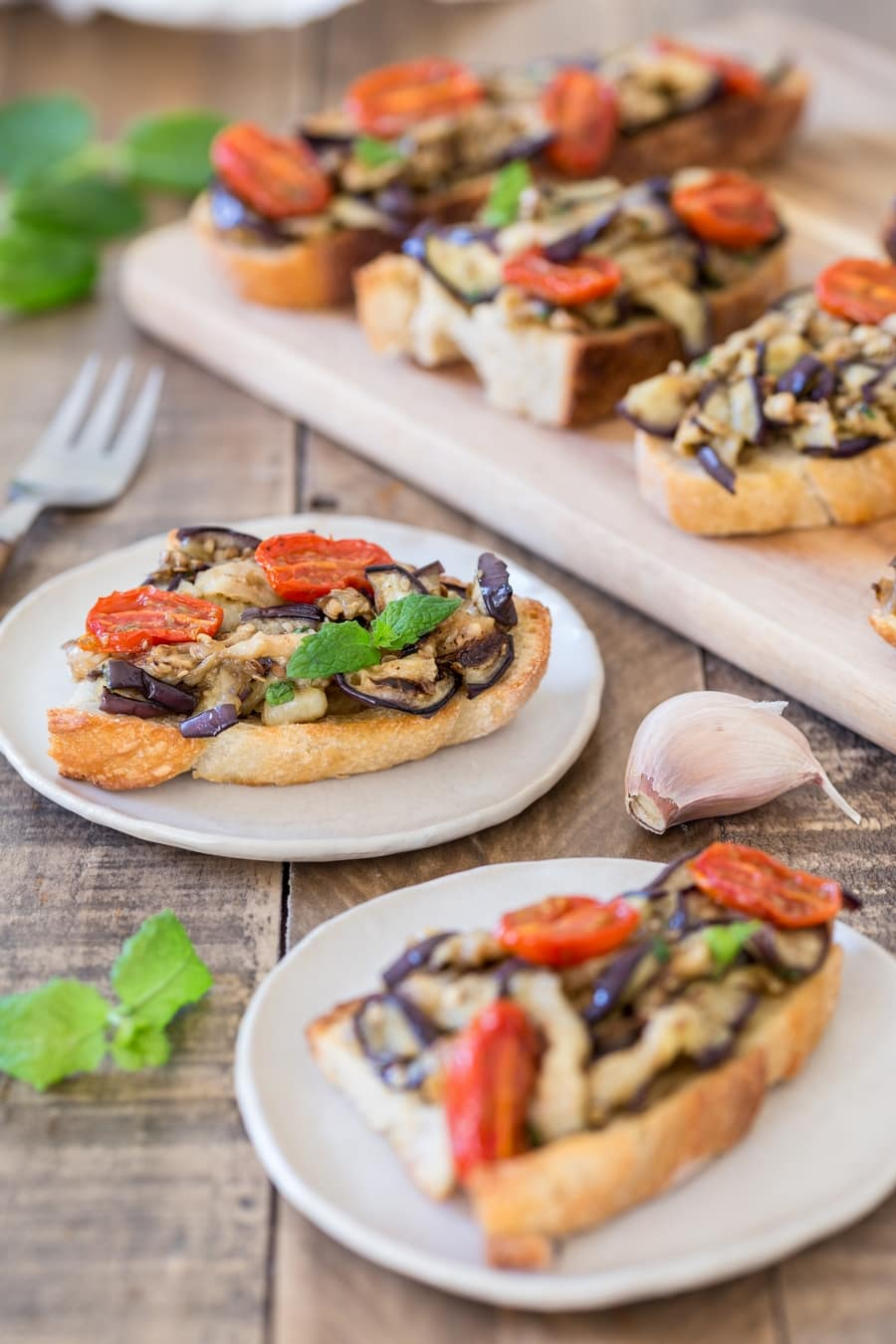Slices of toasted bread topped with grilled eggplants and roasted cherry tomatoes.