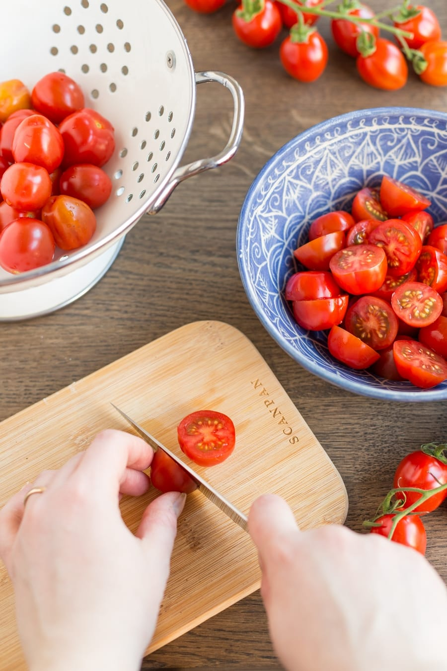 Cutting cherry tomatoes in half on a wooden board, placing cut tomatoes in a bowl.