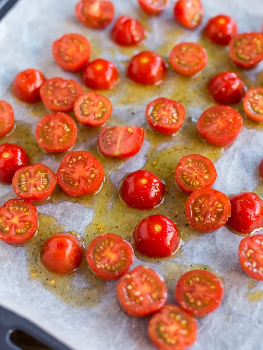 Raw cherry tomatoes on an oven tray about to get in the oven for roasting.
