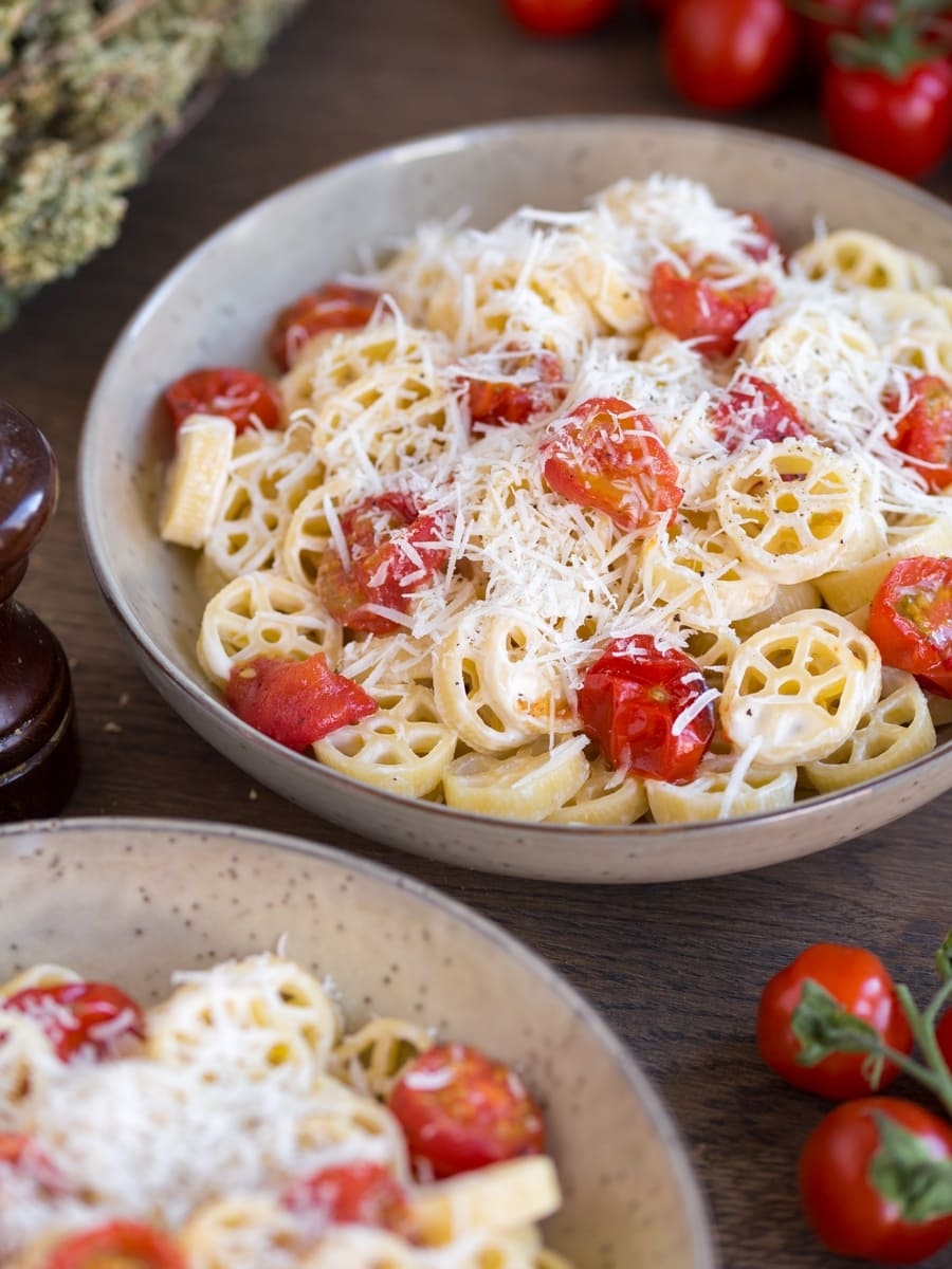 Two bowls of roasted cherry tomato pasta in beige serving bowls.