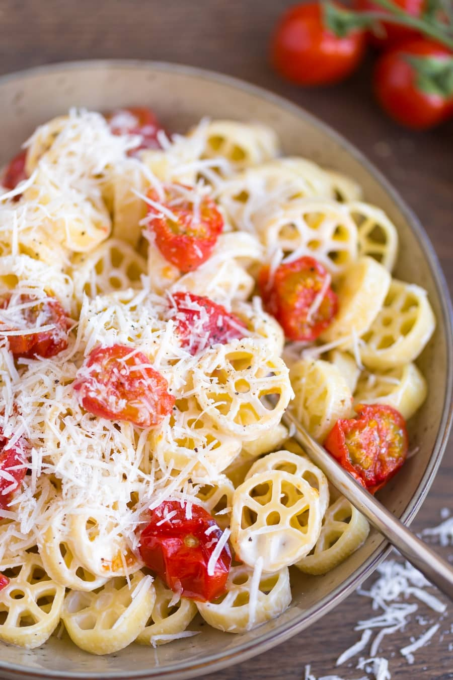 Creamy pasta with overn-roasted cherry tomatoes closeup.