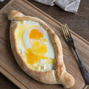Fully baked adjaruli khachapuri with raw egg yolk on top.