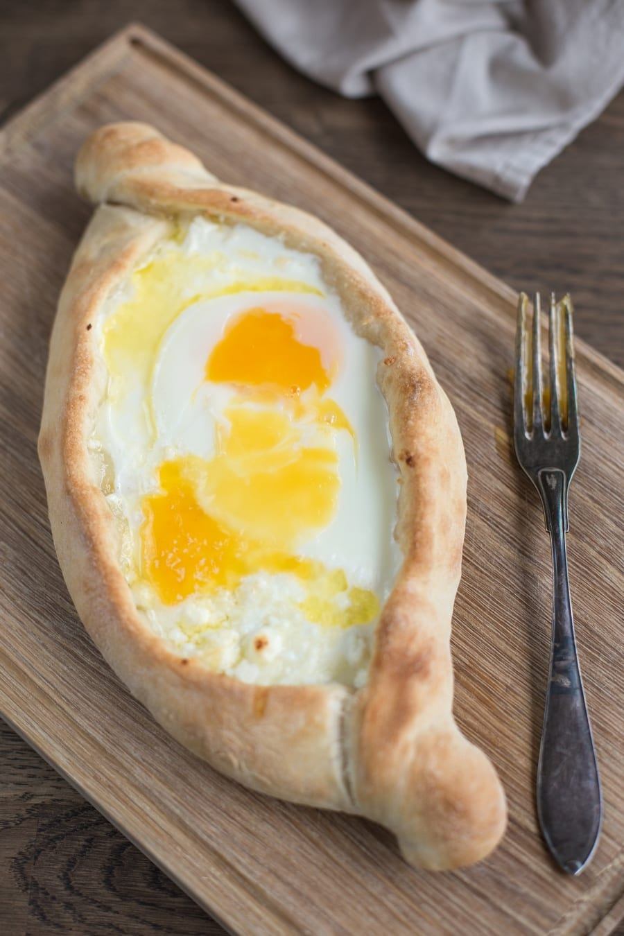 Sourdough khachapuri adjaruli on wooden board.