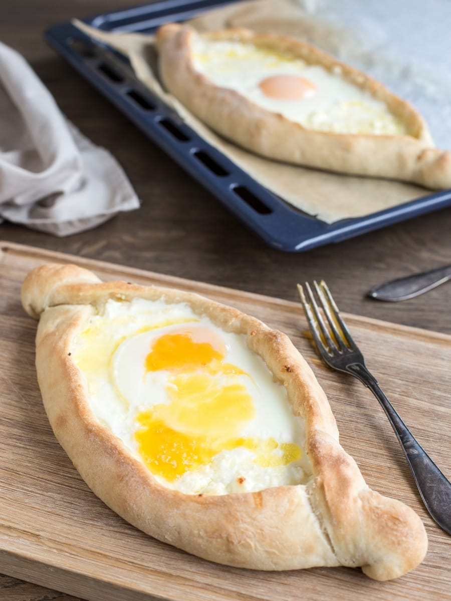 Georgian bread khachapuri adjaruli, one on wooden board, one on oven tray.