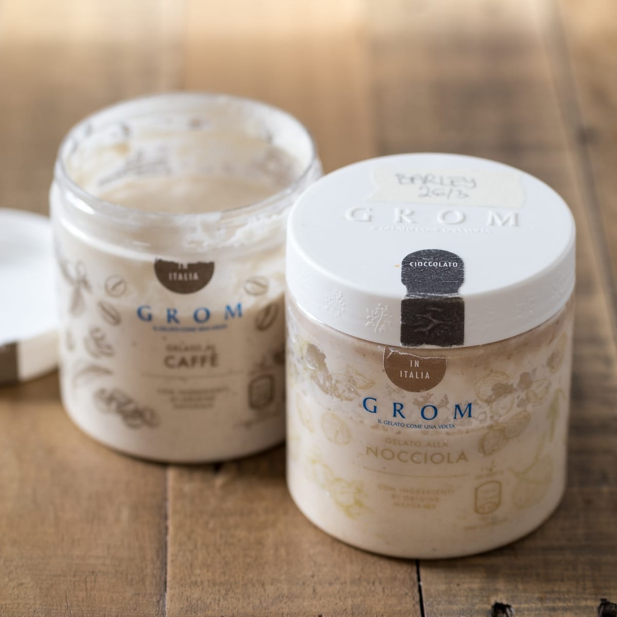 Two plastic gelato jars containing sourdough starter.