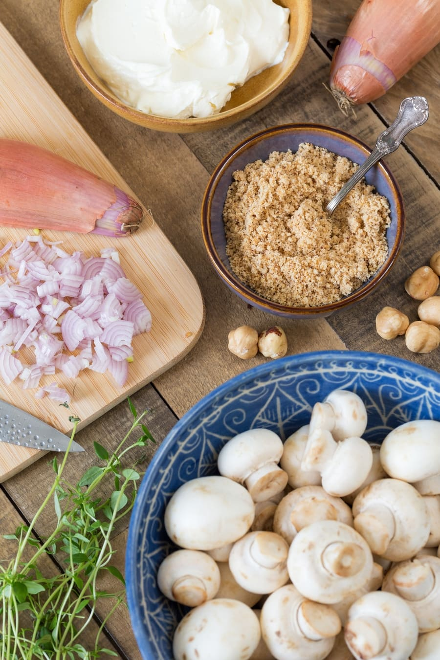 Flatlay image of ingredients needed for the preparation of stuffed mushroom caps.