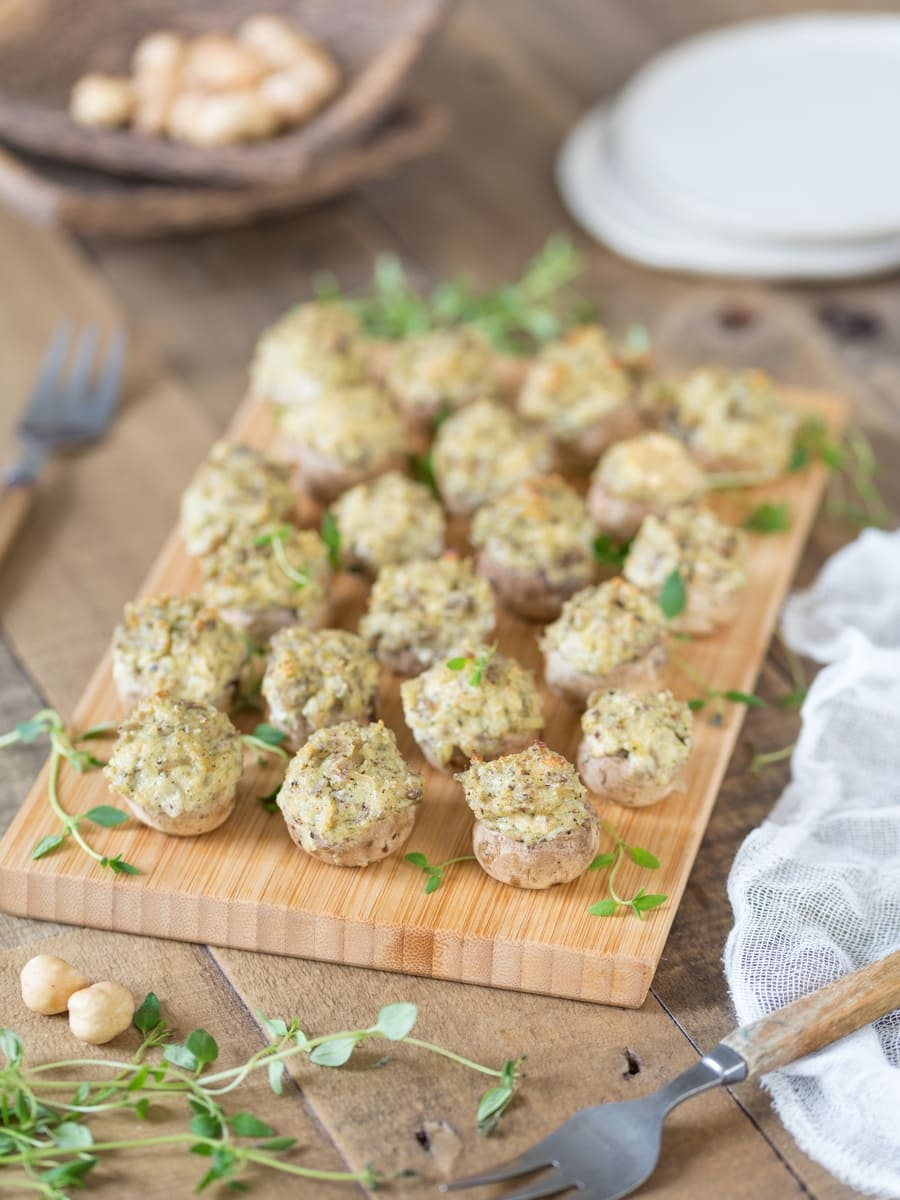 Vegetarian stuffed mushrooms with cream cheese and hazelnut on a bamboo tray.