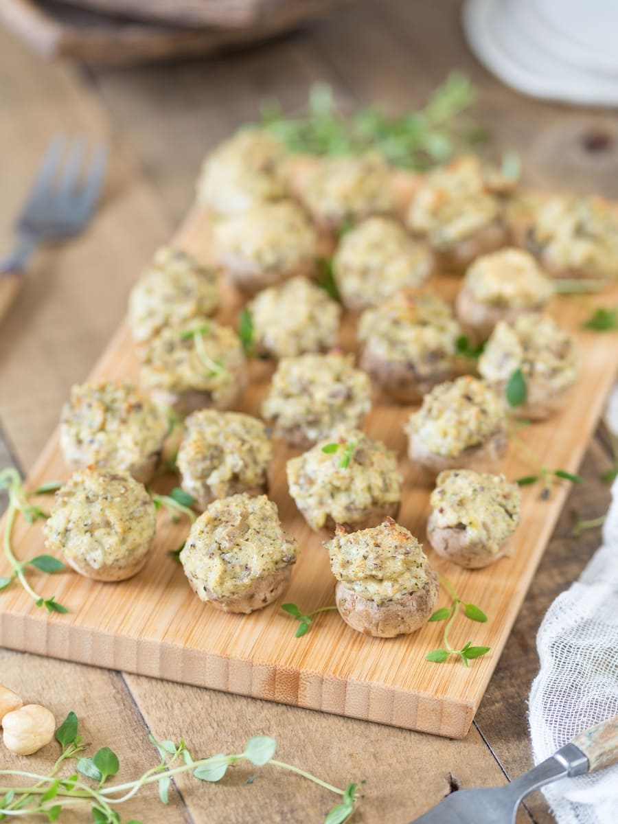 Baked stuffed mushrooms with a cream cheese and hazelnut filling served on a wooden tray.