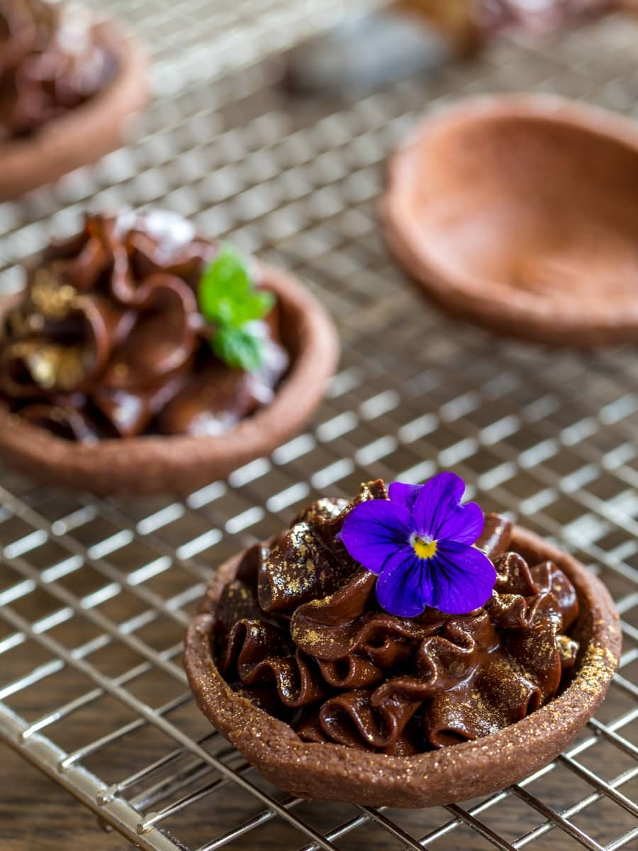 Chocolate mascarpone mousse tarts decorated with flowers and edible gold.