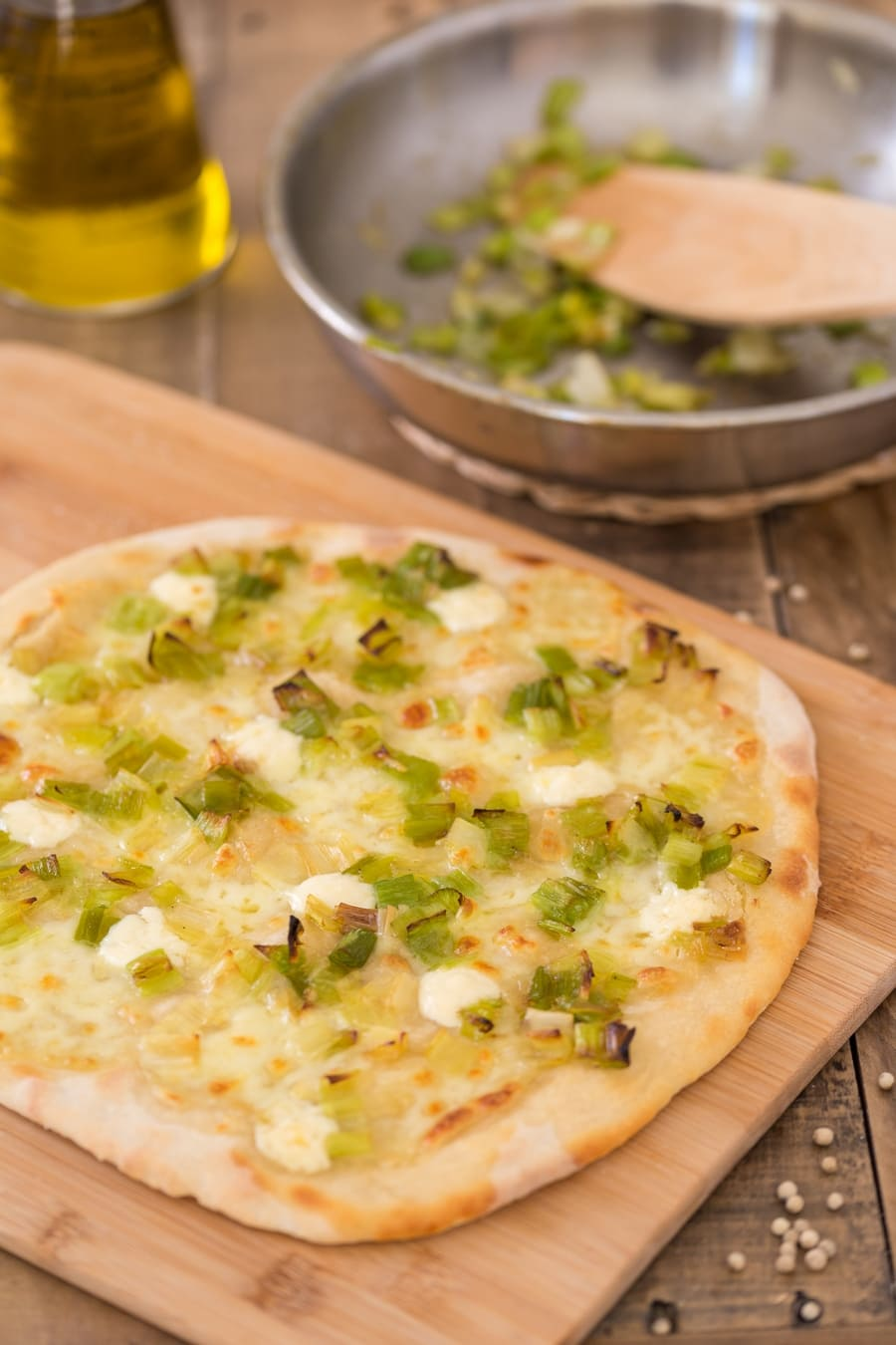 Stone-baked leek mascarpone pizza bianca on a wooden board.