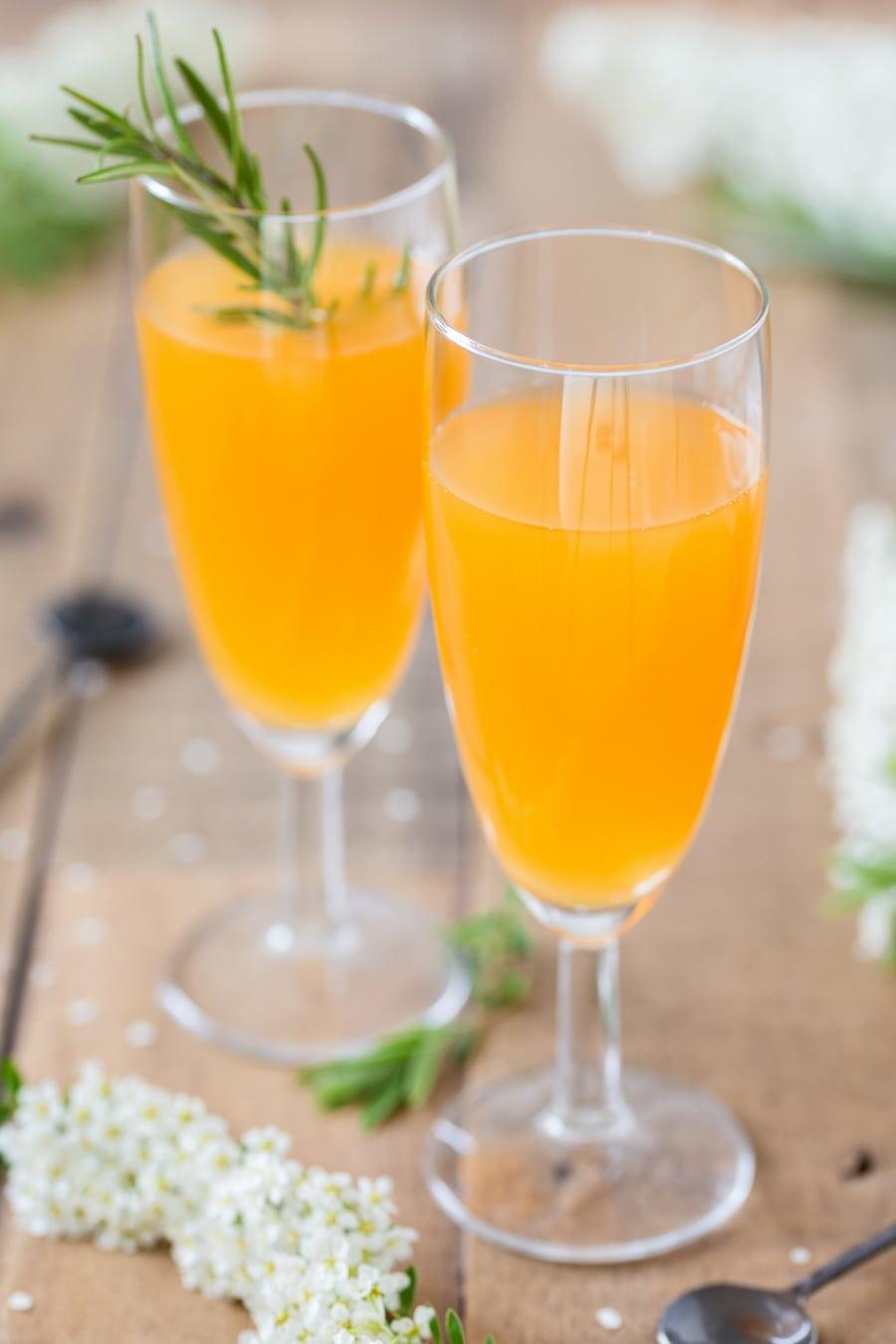 Mango cider bellini in champagne glasses.