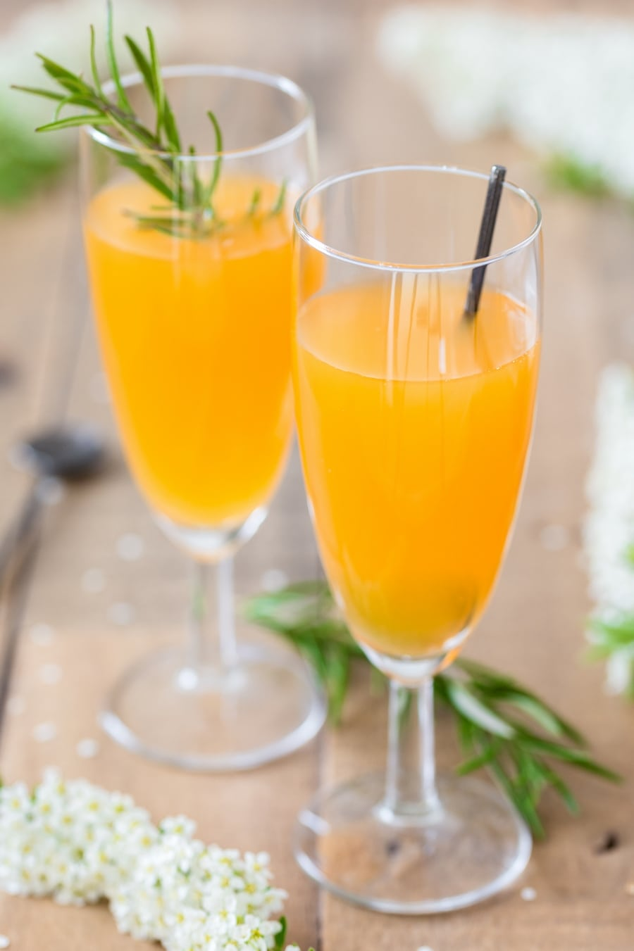 Champagne glasses with mango cider cocktail.