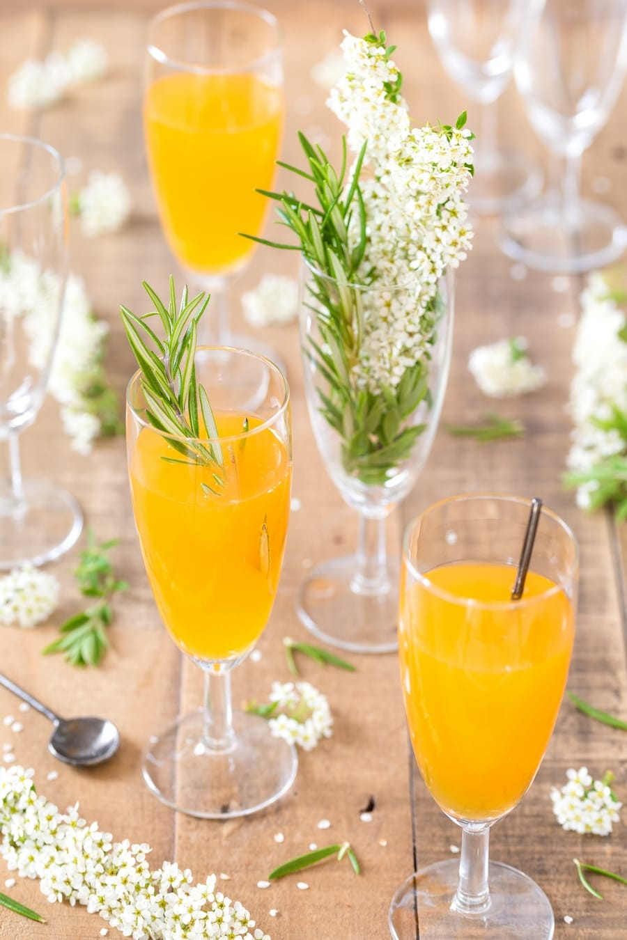 Several flutes with mango cider bellini and flowers.