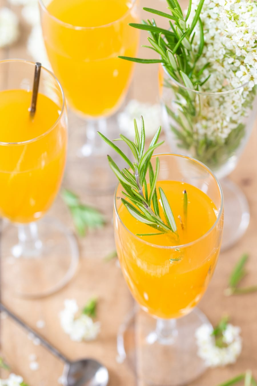 Mango cider bellini in flutes, served with rosemary sprig.