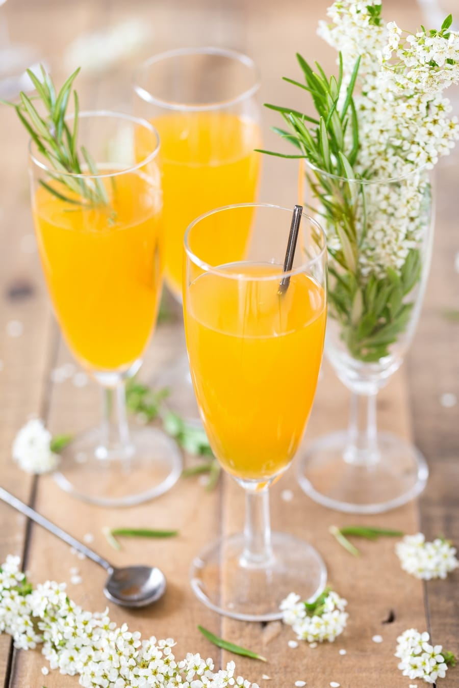 Three champagne glasses with mango cider bellini cocktail.