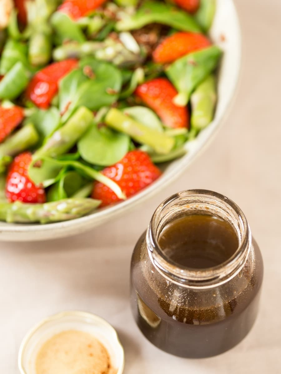 Balsamico vinaigrette dressing in a jar next to salad bowl.