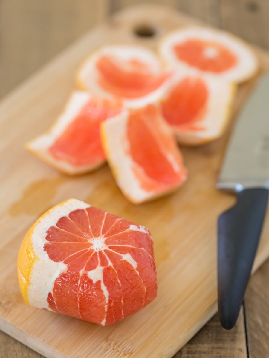 Grapefruit being peeled witha knife.