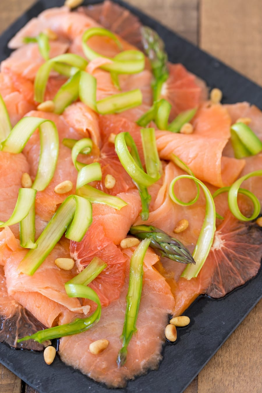 Raw asparagus salmon carpaccio with thinly sliced red grapefruit.
